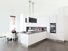 Clean lines,  white+wood+metal+glass, integrated appliances, colored countertop with white cabinets, flush & featureless cabinet doors