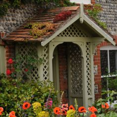 """Overstrand is a charming coastal village  in  North Norfolk, England; christened """"Poppyland"""" in 1883 by Victorian journalist Clement Scott. The back lanes of Overstrand, such as the one above, contain quaint cottages and lovely gardens. The heart-shaped plants on the porch roof are House Leeks."""