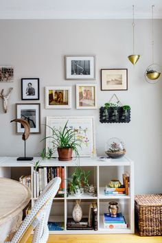 """A mixture of items hang on the wall gallery from travel photos, images from Victoria's family, and even a piece of driftwood. On the right, beautiful <a href=""""http://www.urbanoutfitters.com/urban/catalog/productdetail.jsp?id=35783802&parentid=SUGGESTIVE+SEARCH+RESULTS&q=hanging"""" target=""""_blank"""">brass planters</a> add in some life. They call this area the """"garden corner."""""""