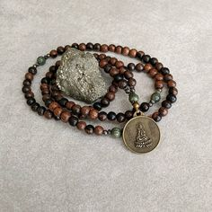 This wood mala necklace is handcrafted with 8 mm natural tiger ebony and serpentine gemstones with an antiqued brass pendant featuring Quan Yin on one side and a dragon on the other side. - Packaged with a mala bag for safekeeping. - Includes gift box ready for giving. - Measures