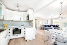 cuisine ouverte sur le salon spacieux aménagé avec un canapé d'angle gris et beaucoup de coussins