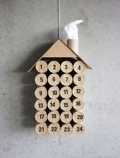 "diy advent calendar made from toilet paper rolls, glued down to a backing sheet, then put a gift in each or a coupon for activity, and seal with brown paper circles. Vinyl stick-on numbers: or draw on with a sharpie. ""Roof"" is a corner from a box, and the chimney has tissue paper ""smoke""... No matter how ""not crafty"" you think you are, You can make this."