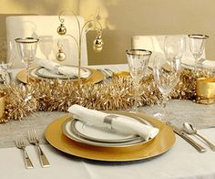 Christmas Table Ideas: Decorating with Silver and Gold - Gold chargers are highlighted by silver accented china and crystal. In place of a pricey metallic runner, an inexpensive silver curtain panel was used. The silver and gold garland draped across the center of the table, brings it all together.