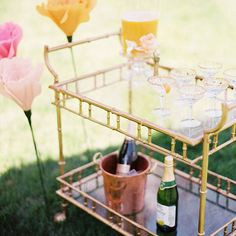 Get the party rolling with a portable bar cart. This gold one is both fashionable and functional. Use it to create a self-serve drink bar complete with punch, champagne, and sparkling juice.
