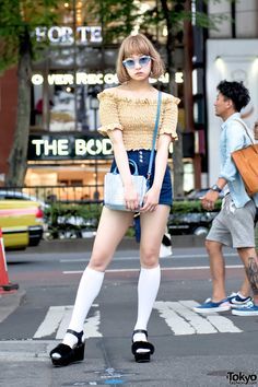 19-year-old Toko on the street in Harajuku wearing an off the shoulder floral top from LilLilly with Heather denim shorts, WEGO platform sandals, Bubbles accessories, and a Vivienne Westwood purse