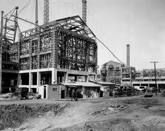 (ca. 1928) - Two men wearing suits walk past the construction site of the Powell Library building. On the right is the can be seen of Royce Hal still under construction.
