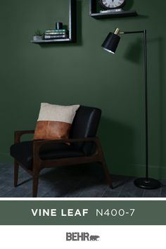 A dark green wall color, neutral black accents, and warm wood tones make for a stunning combination. BEHR® Paint in Vine Leaf forms the base of this sleek and sophisticated space. Click below for color details. Behr Paint Colors, Wall Paint Colors, Accent Wall Bedroom, Green Wall Color, Paint Colors For Home, Dark Green Walls, Bedroom Green, Green Painted Walls, Green Accent Walls