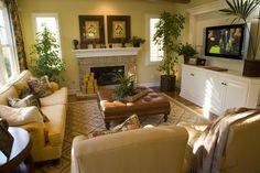 This living room is filled detail: light yellow fabric chairs and couch,large leather ottoman doubling as coffee table, white cabinetry, and stone brick hearth.