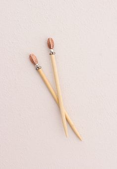 "Warm and earthy antiqued copper uniquely shaped with etched petals, atop a set of two 5"" blonde sticks."