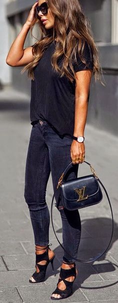 26 Great Fall Outfits: Ideas To Try Already This Autumn/Winter Season: Woman on the sidewalk wearing black skinny jeans, black T-shirt and black strappy statement heels with a black Louis Vuitton Vivienne LV bag