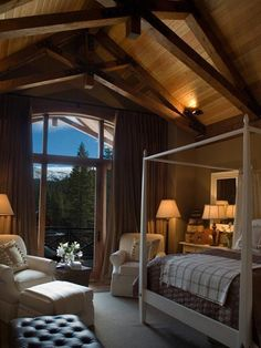 High pine ceilings stacked with timber scissor trusses make this master bedroom a mountain retreat. Cocoa-colored walls, white furniture and contrasting textures deliver a cabin feel.