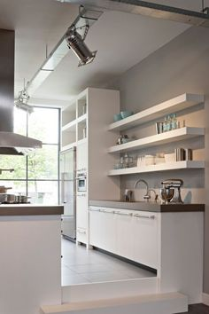 Open shelving and uncovered windows keep this kitchen feeling light and relaxing