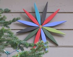 This is a hanging wooden starburst made from recycled pine for use as a colorful…