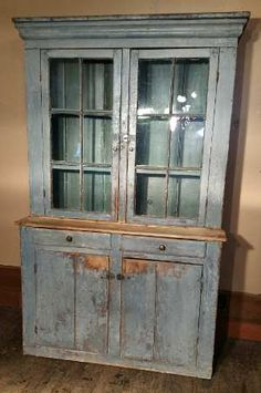 """Piece 19th C. Stepback Cpd. - in old gray-blue paint. 2 upper doors have 6 lites containing old bubbly glass. Bottom is 2 drawers over 2 doors concealing a compartment with one shelf. Left side has black over the gray which can easily scrape off. The right side has the original red paint. Interior has a newer gray paint. Great cornice molding. A solid primitive stepback cupboard with paint losses, repairs, wear and losses. Measures: 85"""" tall x 52"""" wide x 20"""" deep"""