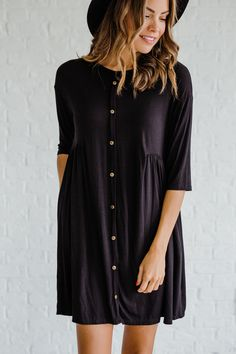 The darling Carmen Black Dress is a perfect blend of comfort and style. The buttons add an adorable touch to this closet staple. The half-cinched waist makes for a great fitted effect while keeping the silhouette loose and comfy. Wear this as a dress or even pair it with some leggings through the cold fall and winter months!
