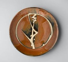 Hamada Shoji a round Dish with resist flower stem design stoneware, persimmon glaze with the wax-resist motif in the well Diameter 12 1/4in. (31.2cm)