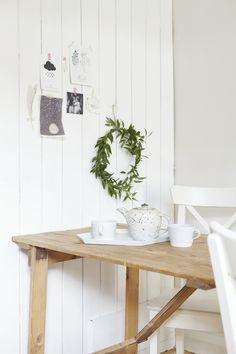 Białe deski na ścianie i drewniany stół w aranżacji rustykalnej jadalni