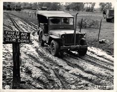"""1944- U.S. jeep passes sign on muddy French road which reads """"This Is No Lincoln Highway… Slow Down""""."""