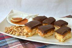 Prajitura Snickers cu caramel si arahide reteta pas cu pas. Un blat fraged, o crema spumoasa cu unt de arahide, caramel si o glazura generoasa de ciocolata