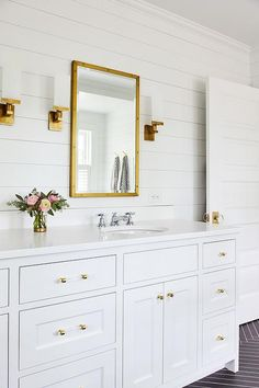 Stunning white bathroom with gold accents boasts a Restoration Hardware Rivet Mirror hung from a white shiplap wall between antique brass sconces.
