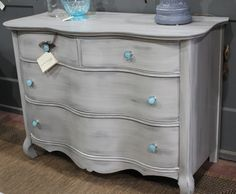 Antique bow front dresser painted in General Finishes Seagull Gray, Halcyon Blue, and Snow White Milk Paints, distressed, and finished with GF High Performance Top Coat. New blue glass knobs.