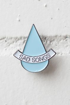 "Soft enamel lapel pin in black, white and blue featuring a new take on a favourite slogan - Sad Songs. 1"" wide. Comes on card backing."