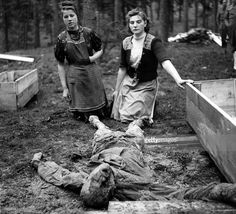 War and Conflict, World War Two, Atrocities, pic: 1945, The body of a slave worker having been murdered by German Nazis at Saltau is shown to two local German women forced by the British see the atrocity, and rebury the victims properly