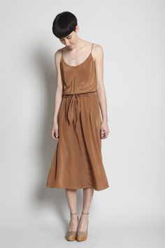 Long and flowing silk crepe de chine dress with waist tie, attached at sides. Camisole top with spaghetti straps. Elastic waist. Slips on. Dry clean.