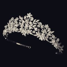 You will dazzle in this royal flowered tiara. Faux pearls and Swarovski crystals…
