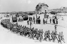 June 6, 1944: German prisoners-of-war march along Juno Beach landing area to a ship taking them to England, after they were captured by Canadian troops at Bernieres Sur Mer, France
