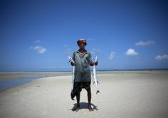 Fisherman with two fishes in his hands at Nungwi beach,  Zanzibar, Tanzania