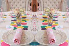 mesa posta estilo carnaval com forro branco círculos coloridos de papel ao centro, louça branca, guardanapo rosa claro e arranjo de flores colorido.