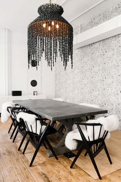 """The conference room celebrates the ceiling height Fister loves so much about the space. """"Rooted with an oversize beaded chandelier (sourced through Anthropologie) and our signature Fornasetti..."""