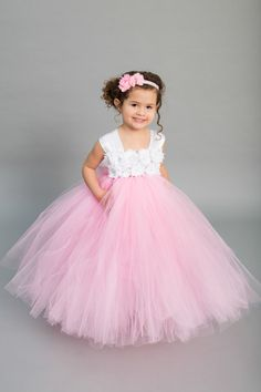 Make your wedding stand out with this beautiful White and Pink Flower Girl Dress. This multilayer dress is made with yards and yards of premium soft tulle. Embellished with white flowers featuring rhinestone encased faux pearls. The double white satin straps lay over the shoulders and tie in the back into one large bow. The listed length is for a measurement from armpit to hem. **Please measure from underneath the armpit to the floor or top of foot.** Each dress is handmade as ordered The...