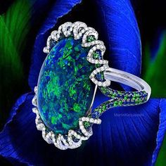 The flashing play-of-color within an opal is the product of light dancing through and bouncing off the silica within the stone.  Martin Katz (over 16ct.) Australian Black Opal Ring.