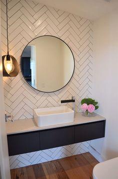 herringbone tile, round mirror, floating vanity, modern bathroom, powder room Visit us at www.ie for more fantastic tiling ideas! Bathroom Mirror Design, Bathroom Interior, Bathroom Lighting, Master Bathroom, Bathroom Mirrors, Bathroom Designs, Bathroom Pink, Bathroom Wall Tiles, Chevron Bathroom