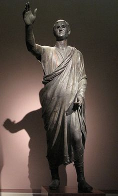 "The Orator, c. 100 BC, an Etrusco-Roman bronze sculpture depicting Aule Metele (Latin: Aulus Metellus), an Etruscan man of Roman senatorial rank, engaging in rhetoric. He wears senatorial shoes, and a toga praetexta of ""skimpy"" (exigua) Republican type.[3] The statue features an inscription in the Etruscan alphabet"