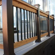 A two tone deck railing is created with a combination of black synthetic posts and balusters with wood rails.