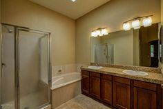 Transitional Master Bathroom with Complex Granite Tile, High ceiling, European Cabinets, complex granite tile counters