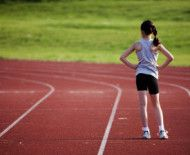 woman standing on race track thinking-when and how to start a running program.