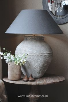I think it would be great to purchase a ginger jar lamp (traditional metal) then wrap rope and glue, then coat with cement.  Then dry brush paint to color desired... voila!!!