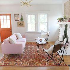 pink sofa, orange accents, gold light fixture
