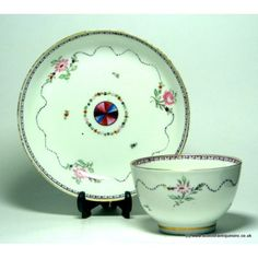New Hall Tea Bowl and Saucer Pattern 338 variant c1790  Painters tally mark # 30 on the base. See 'New Hall' by David Holgate p76 plate 39 for another variation.  Decoration has an undulating line interrupted by sprays containing a pink rose. The centre of both pieces has a wheel in orange, mauve, pink and blue. Floral sectors containing pink roses, orange pimpernels and leaves painted in two shades of green with a mauve garland rim border, gilding to rim and foot of bowl.