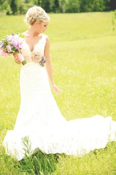 Country wedding pictures in a field are a must. I love her sash with the flowers
