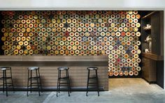 A great solutions to a difficult space, narrow with a large wall. In response the designers created a magnetic wall to store the 565 metal tea tins (with graphic tea cup decaled lids), and a tailored length long walnut table and high chairs for customers to enjoy a warm sip.
