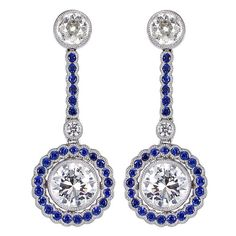 Platinum vintage style drop earrings consisting of 2 bezel set round brilliant cut diamonds having a total weight of 2.71 carats accented by 4 old European and round brilliant cut diamonds having a total weight of .65 carats, bezel set round cut sapphires accents having a total weight of .96 carats. Via 1stdibs.