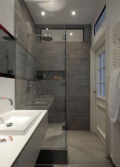 Der extrem breite, hinterleuchtete Spiegel sowie Glasfenster über Tür und Dusche versorgen neben dem eigentlichen Fenster den zuvor dunklen Raum üppig mit Tageslicht.