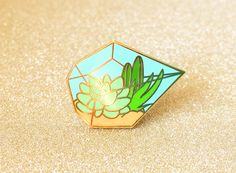 """One terrarium enamel pin, perfect for succulent and cacti enthusiasts. THE NITTY GRITTY ✎ One 1-inch (25mm) hard enamel pin, made from my original illustration ✎ Shiny gold metal✎ One rubber pin back ✎ """"OH PLESIOSAUR"""" stamped on reverse PACKING & SHIPPING Packaged on a sturdy backing card, with a clear plastic sleeve for additional protection. Ships via USPS First Class Mail (arrives in 2-5 days). Priority Mail upgrade (1-3 days) available at checkout."""