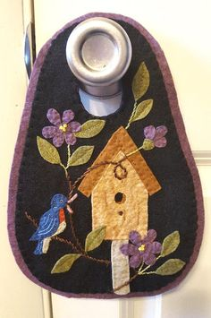 Gina wants to share her *NEW* BIRDHOUSE door hanger with you. So easy to stitch up for display or gift giving. Features a pretty bluebird carrying a worm home to the birdhouse to feed its babies. A lovely vine with plum purple flowers is featured. Make this lovely door hanger using