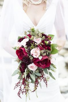 Wedding bouquet with pink and deep red peonies, merlot dahlias, and plump blackberries